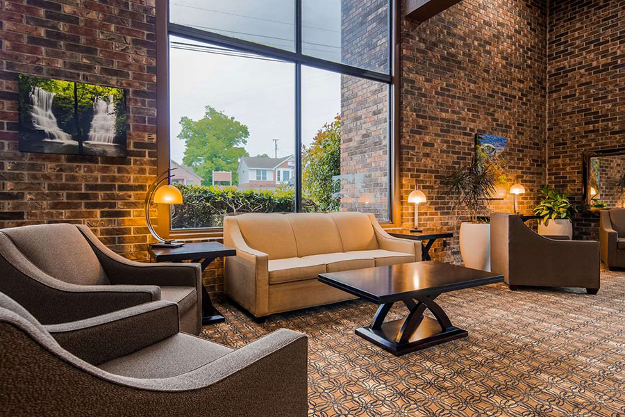 sofa and chair seating by window in lobby of Best Western Sherwood Inn