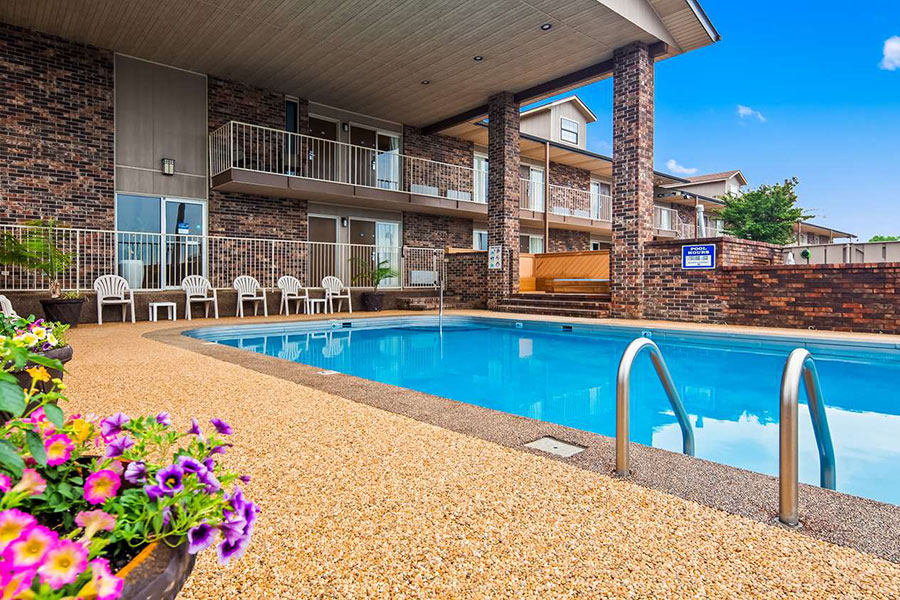 outdoor pool with view of landscaping flowers and patio overhang with chairs underneath at Best Western Sherwood Inn