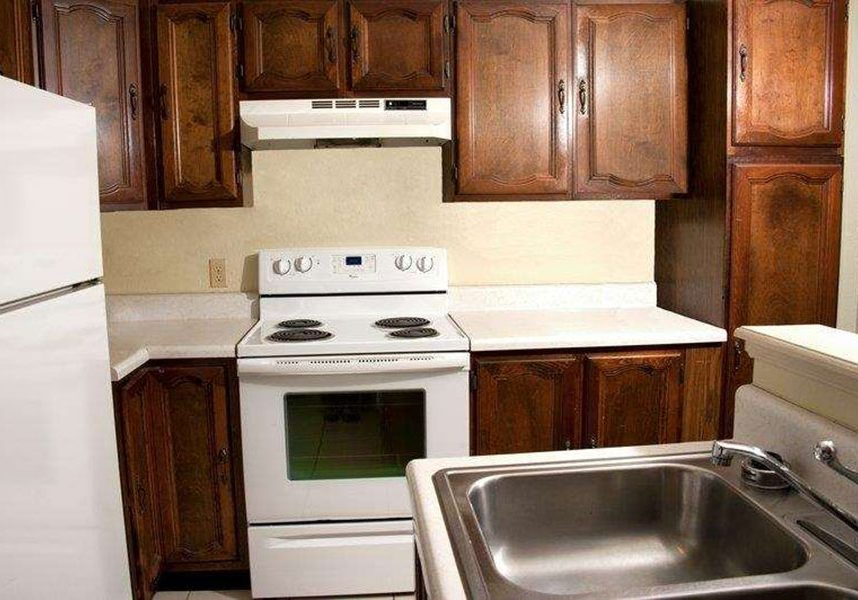 queen suite kitchen including stove, oven, refrigerator, sink, and cabinets at Best Western Sherwood Inn